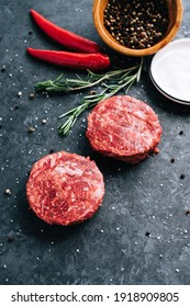 Fresh raw minced beef steak for burgers on black background with rosemary, chili pepper and spice