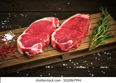fresh raw new-york steak on wooden Board on wooden background with salt and pepper in a rustic style, top view