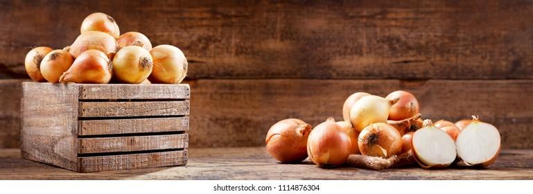 fresh raw onions in a wooden box