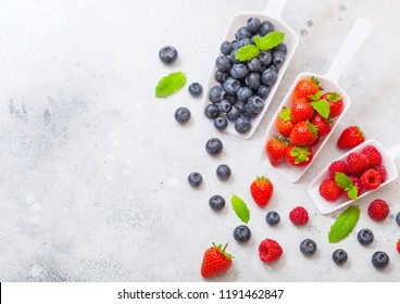 Fresh raw organic berries in white scoop spoon on kitchen table. Space for text. Top view. Strawberry, Raspberry, Blueberry and Mint leaf