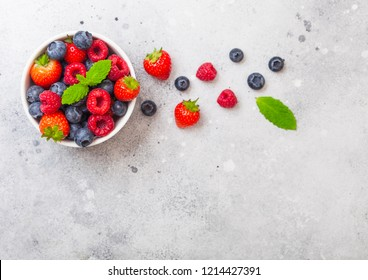 Fresh raw organic berries in white ceramic bowl on kitchen table background. Space for text. Strawberry, Raspberry, Blueberry and Mint leaf