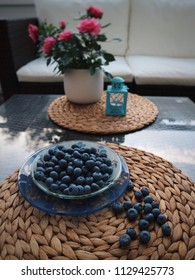 Fresh raw organic blueberries in a bowl. Blueberries on a table. Berries and flowers on a table. Eating outdoors. Side view.