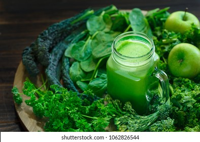 Fresh Raw Organic Green Juice Surrounded by Leafy Greens and Green Apples
