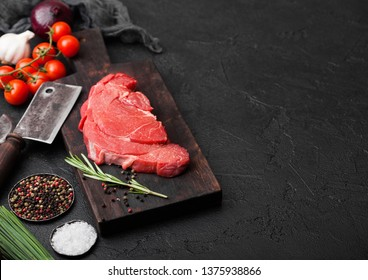 Fresh raw organic slice of braising steak fillet on chopping board with meat hatchets on black stone background. Red onion, tomatoes with salt and pepper.