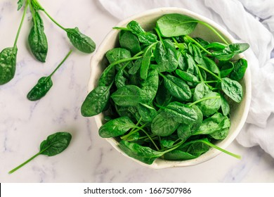 Fresh raw organic spinach leaves with water drops on a white plate on a marble background. Healthy vegan and vegetarian food. The concept of healthy eating. Top view, selective focus