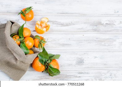 Fresh raw organic Tangerines clementine with green leaves in bag on white wooden table., copy space