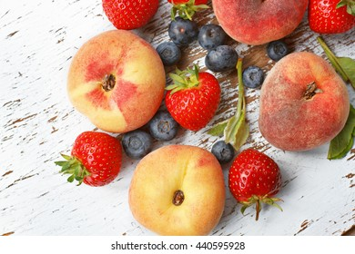 Fresh raw peaches, strawberries and blueberries on table