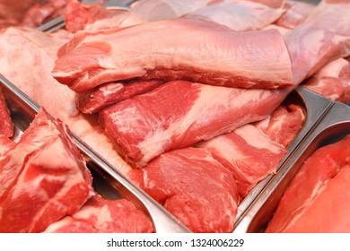 fresh raw pork meat cuts on metal display in the supermarket
