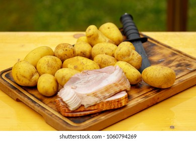 Fresh raw potatoes with meat and knife on wooden table