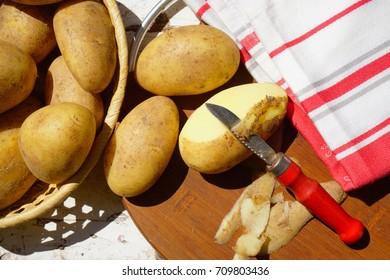 fresh raw potatoes and potato peeler,