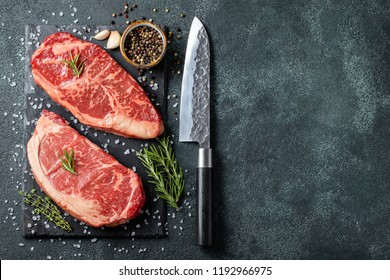 Fresh raw Prime Black Angus beef steaks on stone board: Striploin, Rib Eye. Top view with copy space. On a dark background