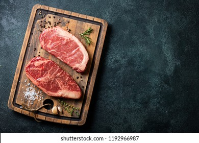 Fresh raw Prime Black Angus beef steaks with spices on wooden board: Striploin, Rib Eye. Top view with copy space. On a dark background