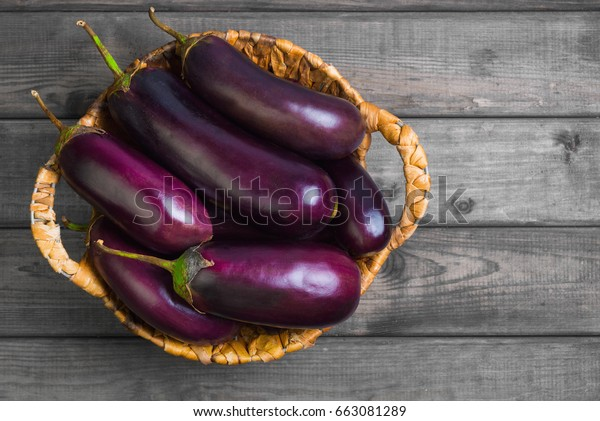 グレイの木の背景に茄子の特別な籐籠に生の紫茄子。平面図、空白。