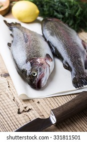 Fresh raw rainbow trout on parchment on wooden rustic table, selective focus