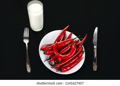 Fresh raw red chili pepper on a white plate. Cutlery - fork and knife on the table and a glass of milk. Spicy food on black background