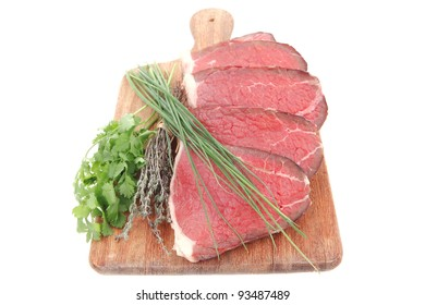 fresh raw red meat with thyme and chives on wooden plate isolated on white background