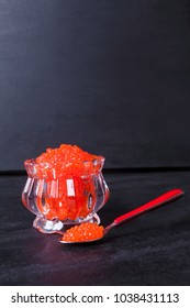 fresh raw red salmon caviar in white crystal bowls with small spoon on blackwooden background