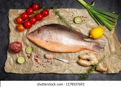 Fresh raw red snapper fish with spices , herbs and vegetables for cooking on brown backing paper . Top view.
