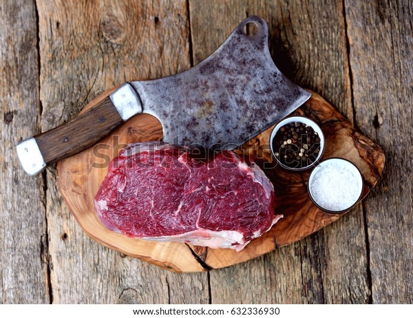 Fresh raw roast beef on a cutting board on an old wooden background. Rustic style.a