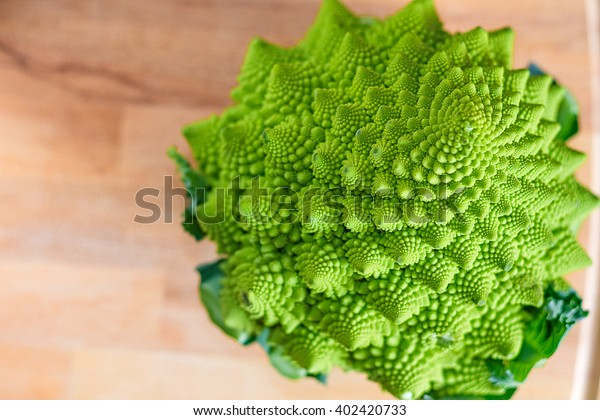 Fresh raw Romanesque cauliflower on a wooden chopping board. Selective focus.