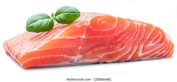 Fresh raw salmon fillet decorated with fresh basil on white background.
