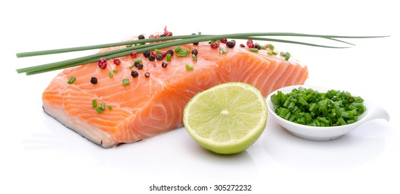 Fresh raw salmon fillet with herbs, lemon and spice, isolated on white