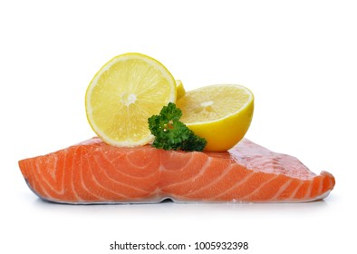 Fresh raw salmon fillet with lemons isolated on a white background.