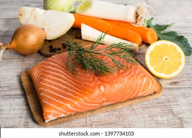 Fresh raw salmon fillet and fresh vegetables.