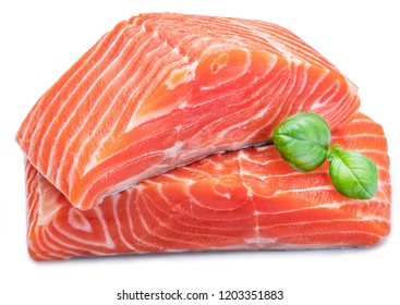 Fresh raw salmon fillets  decorated with green basil on white background.