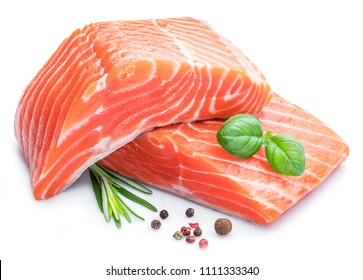 Fresh raw salmon fillets with herbs and spices on white background.