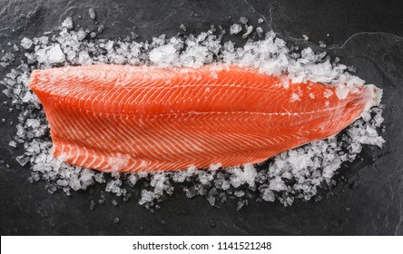 Fresh raw salmon fish steak on ice over dark stone background. Creative layout made of fish, top view, flat lay