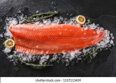 Fresh raw salmon fish steak with spices on ice over dark stone background. Creative layout made of fish, top view, flat lay