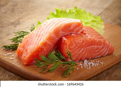 fresh raw salmon on wooden cutting board