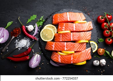 Fresh raw salmon red fish fillet on black background, top view