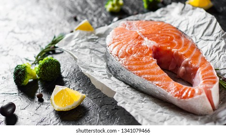 fresh raw salmon steak with broccoli, lemon, olive, pepper and aromatic herbs on the dark background