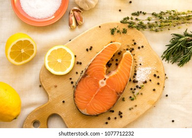 Fresh raw salmon steak with lemon, olive oil and spices on rustic wooden background. Ingredients for making healthy dinner. Healthy diet concept.