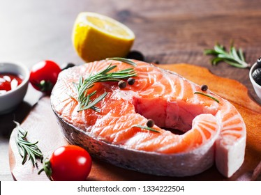 fresh raw salmon steak with tomato, lemon, olive, pepper, sauce and aromatic herbs on the wooden table background