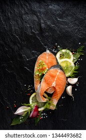 Fresh, raw salmon steaks with the addition of slices of lemon, garlic, onion, herbs and spices on a black stone background, top view. Seafood, fresh fish and ingredients for cooking