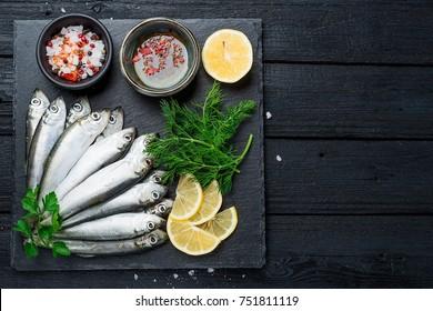 Fresh raw sardines on a dark background, top view.