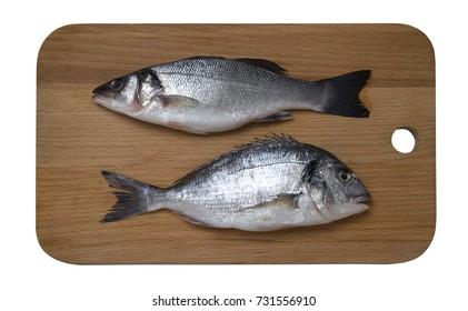 Fresh raw sea bass and dorado fish on wooden cutting board, top view