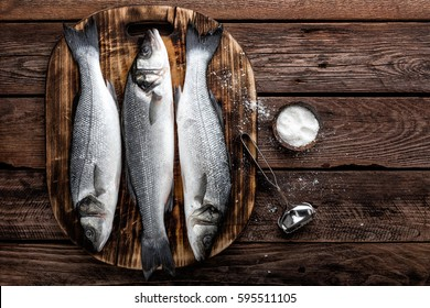 fresh raw sea bass fish on wooden cutting board cooking concept on a dark wooden background top view