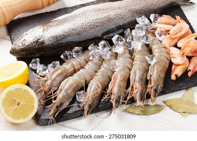 Fresh raw sea food with spices on wooden table background