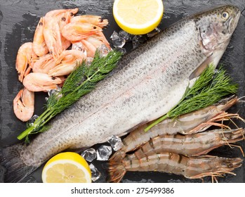 Fresh raw sea food with spices on black stone background. Top view