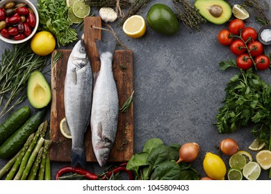 Fresh raw seabass and ingredients for cooking: rosemary, thyme, lime, lemon, greens and vegetables. Top view, copyspace