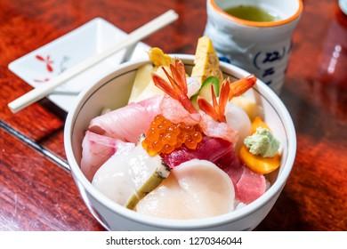 Fresh raw seafood mixed rice bowl (Kaisen-don/ Japanese tasty food), Japanese Rice with sashimi of tuna, Maguro, Otoro, salmon, squid, shramp.