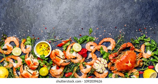 Fresh raw seafood - shrimps and crabs with herbs and spices on dark gray background. Copy space.