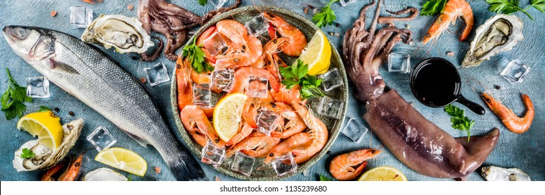 Fresh raw seafood squid shrimp oyster mussels fish with spices of herbs lemon on a light blue background copy space top view  banner