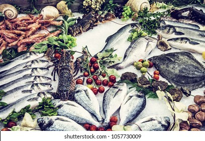 Fresh raw seafoods on counter in restaurant. Food theme. Mediterranean specialties. Blue photo filter.
