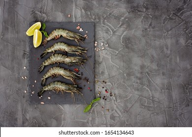 Fresh raw shrimp prawns with lime and spices on a stone board on a gray concrete background. Healthy seafood is a source of protein. Flat lay. Copy space.