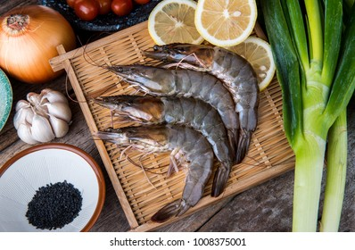 Fresh raw shrimps set with vegatables on the bamboo basket ready for cooking.